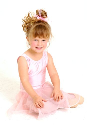 Little smiley girl wearing a pink ballet outfit is sitting on the floor