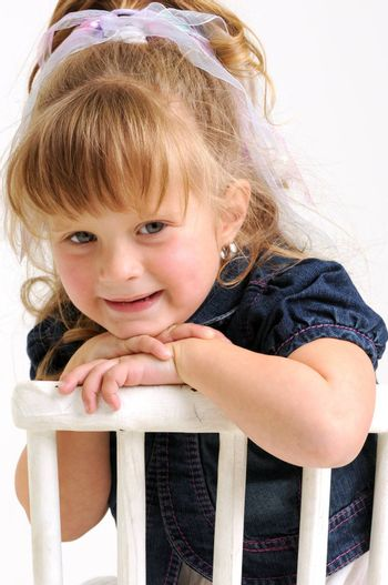 young pretty blond girl with blue dress sitting on a white chair and smiling