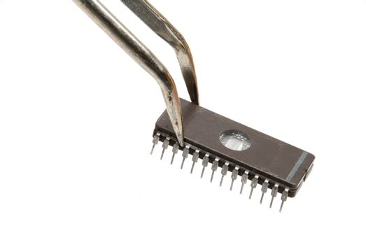 A computer chip being held by tweezers.