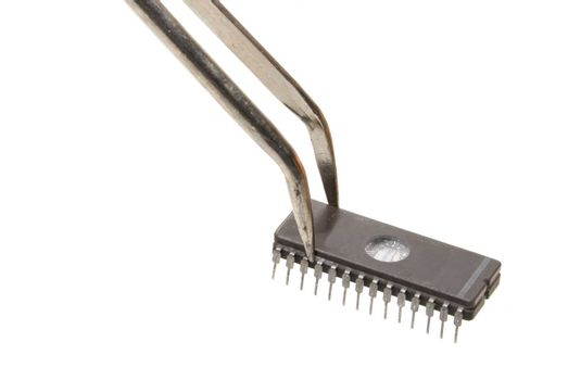 A computer chip being held by a pair of tweezers.