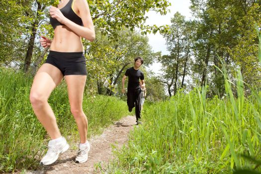 Friends in fitness clothing running on pathway
