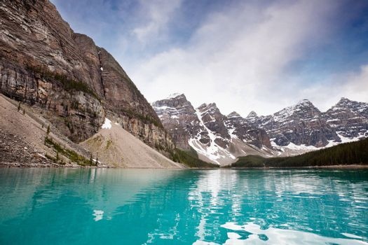 Scenic shot of calm blue water and mountain range against sky
