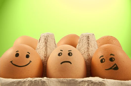 Close and low level of several brown eggs with painted faces against green and yellow light effect background