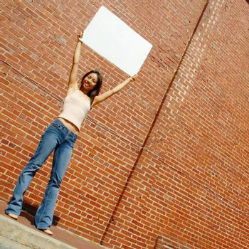Fashionable girl with blank white poster against brick wall.