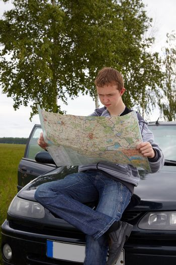 Traveling. Young driver with maps