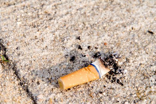 A discarded cigarette butt on a sidewalk.