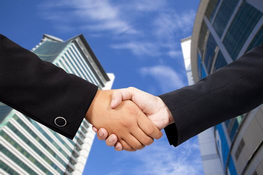 Business people shaking hands against blue sky and modern building