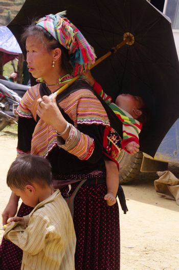 Woman flowered Hmong .Near her ,her son and she carries in her back her baby .She came from far in the mountains this Saturday at Can Cau market shopping