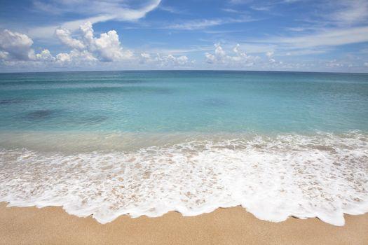 Empty beach with white wave spray