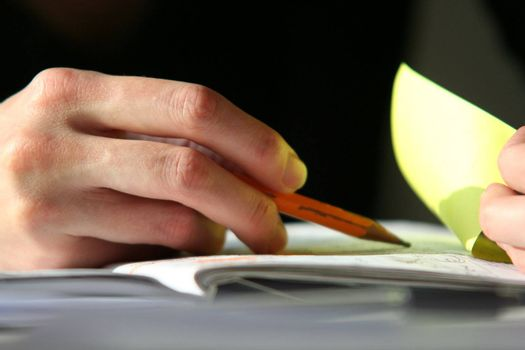 Young woman hand close-up with pencil and notebook