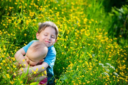 Brother and little sister playing in green grass at sunny summer day.
