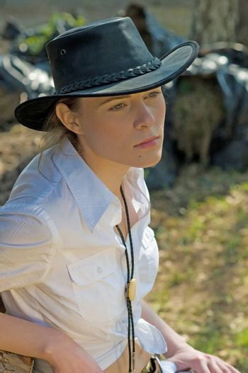 Portrait of a woman in a white shirt and cowboy hat on a ranch.