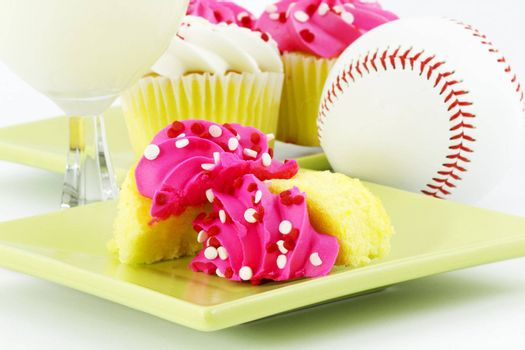 Vanilla cupcakes with pink icing, white milk, and a baseball suggest a festive, after game celebration