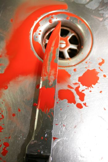 Illustrative styled image of a bloody knife over a plug hole in a stainless steel sink. Knife covered in blood.