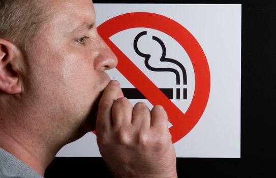 A man smoking a no smoking sign.