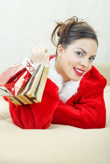 Smiling lady in the red furry Santa Claus costume laying indoors and holding bags with gifts