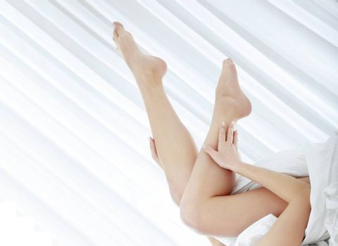Shoeless of the woman laying on the bed in the bedroom. Close-up photo