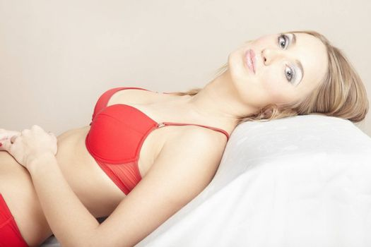 Relaxing woman in the red lingerie laying indoors. Natural colors