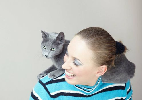 Cat playing on the back of laughing woman indoors