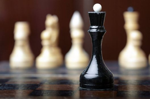 Chess game. Black queen against the group of white cheesmen. Close-up horizontal photo