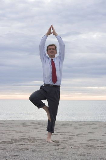 Businessman doing yoga on a beach
