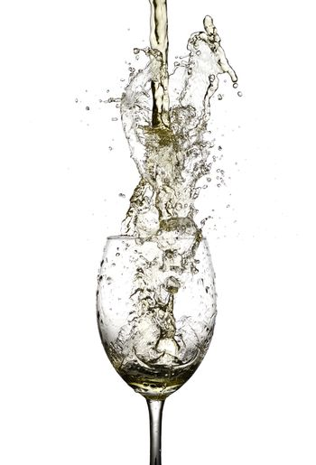 white wine being poured in to a wine glass from a height
