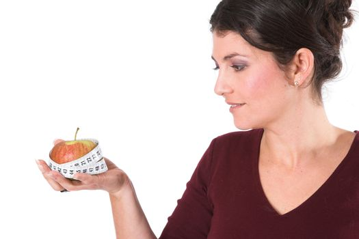 Woman holding an apple in her hand with a measuring tape around it