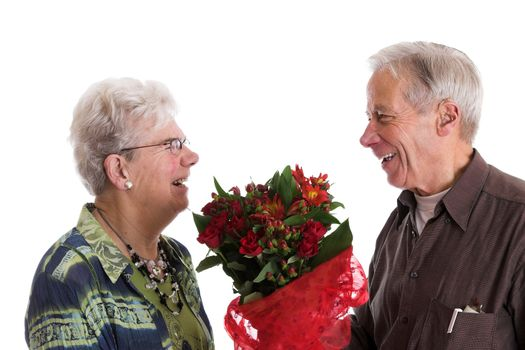 Cute elderly couple during valentines day; the man is giving his wife flowers