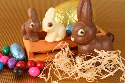 Various colors and shaped easter eggs and bunnies on a gold background