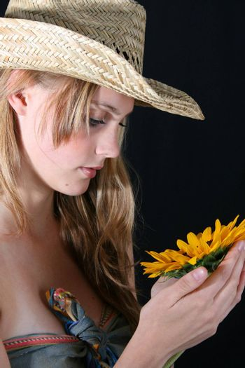 Beautiful young female model holding a sunflower