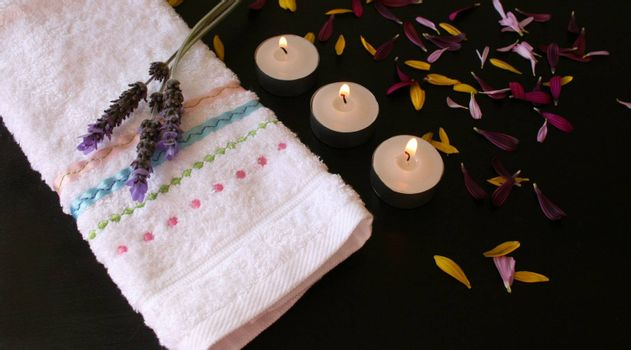 Candles and petals on a brown surface next to a hand towel