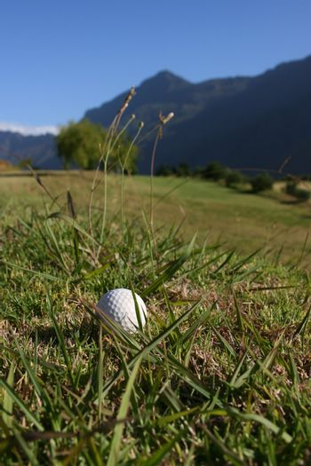 Golf Ball on a golf course with a mountain range in the background