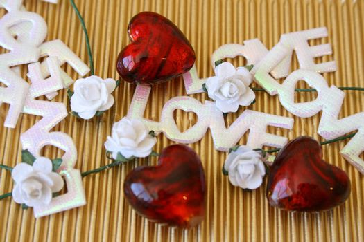 Glass hearts, roses and the word love on a golden background