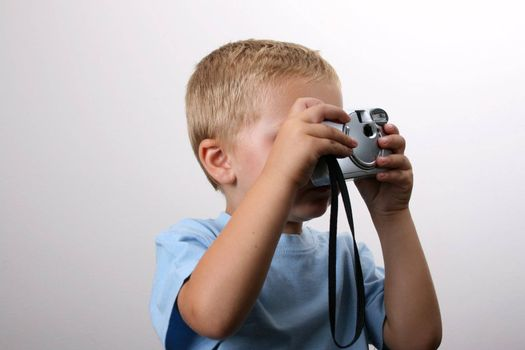 Shy toddler holding a silver camera, looking at his object