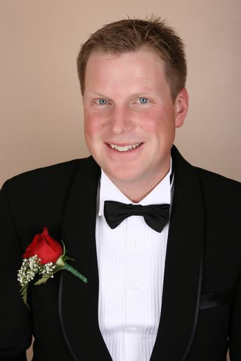 Smiling groom on his wedding day wearing a red rose corsage
