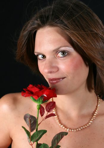 Beautiful young woman with a red rose and pearls