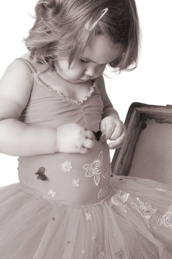Toddler ballet girl looking at her costume