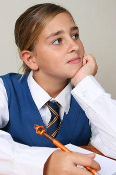 Teenage School girl busy with her homework, wearing uniform