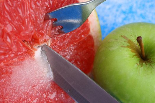 Sliced Pomelo with Sugar and a knife, fork and apple