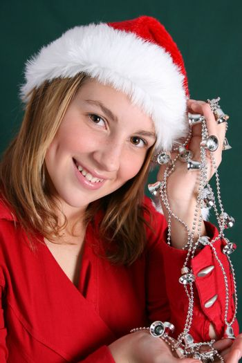 Teenager in red holding a silver string with bells