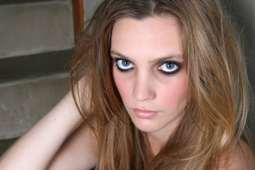 Beautiful female model with blue eyes and dark make up