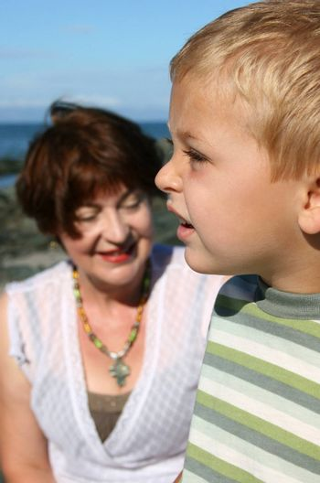 Beatiful grandmother and grandson playing on the beach