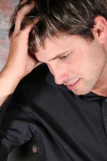 Male model against a rough brick wall background