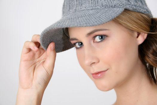 Beautiful young female model wearing a grey hat