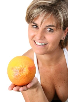 Beautiful mature female holding fruit.  FOCUS ON ORANGE