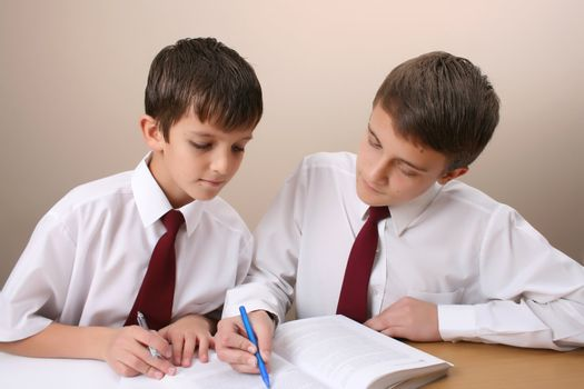 Teenage School boys busy with his homework, wearing uniform