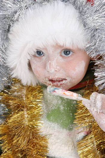 Toddler covered with christmas decorations after baking, eating a lollie