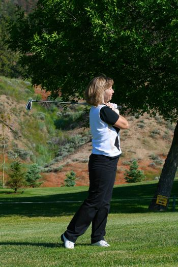 Blond female golfer following her ball down the fairway