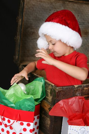 Cute boy sitting inside an antique trunk playing with a decorative christmas ball