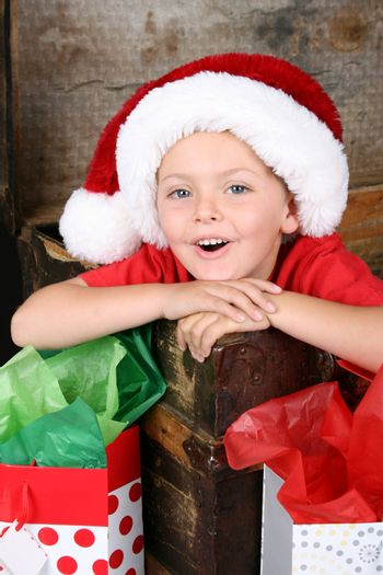 Young boy sitting inside an antique trunk wearing a christmas hat